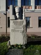 """Oļega Skaraiņa granītā kalto pieminekli. Pieminekli veido trīs masīvu akmens bluķu obelisks ar pulkveža portretu augšdaļā un veltījuma tekstu vidū: """"Fridrihs Briedis. Dz. 1888. g. 23. jūnijā, nošauts 1918. g. 28. augustā Maskavā. Pulkvedis. Latviešu strēlnieku komandieris. Lāčplēša kara ordeņa I, II un III pakāpes kavalieris.""""  """"Tikai tas,  kas dzimis lielās mokās,  pieder mīlestībai."""" (A. Čaks)"""
