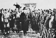 Attēlā kāda padomju kaŗaspēka parāde, kuŗu pieņem tautas kaŗa komisārs L. Trockis (pirmais no labās) un virspavēlnieks J. Vācietis (trešais no labās). Laiks 1918. g. beigas