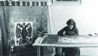 Fotografa Jāņa Rieksta sieva Natālija izšuj 1.Daugavgrīvas latviešu strēlnieku bataljona karogu, tā autors - mākslinieks Ansis Cīrulis