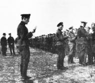 Kapt. Bangerskis apbalvo sava bataljona strēlniekus ar Juŗa krustiem; priekšējā plānā bataljona adjutants virsl. Bolšteins, aiz viņa valsts domes loceklis J. Goldmanis.