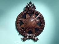 Барельеф нагрудного знака латышских стрелков (на стене зала, выполнен из дерева).